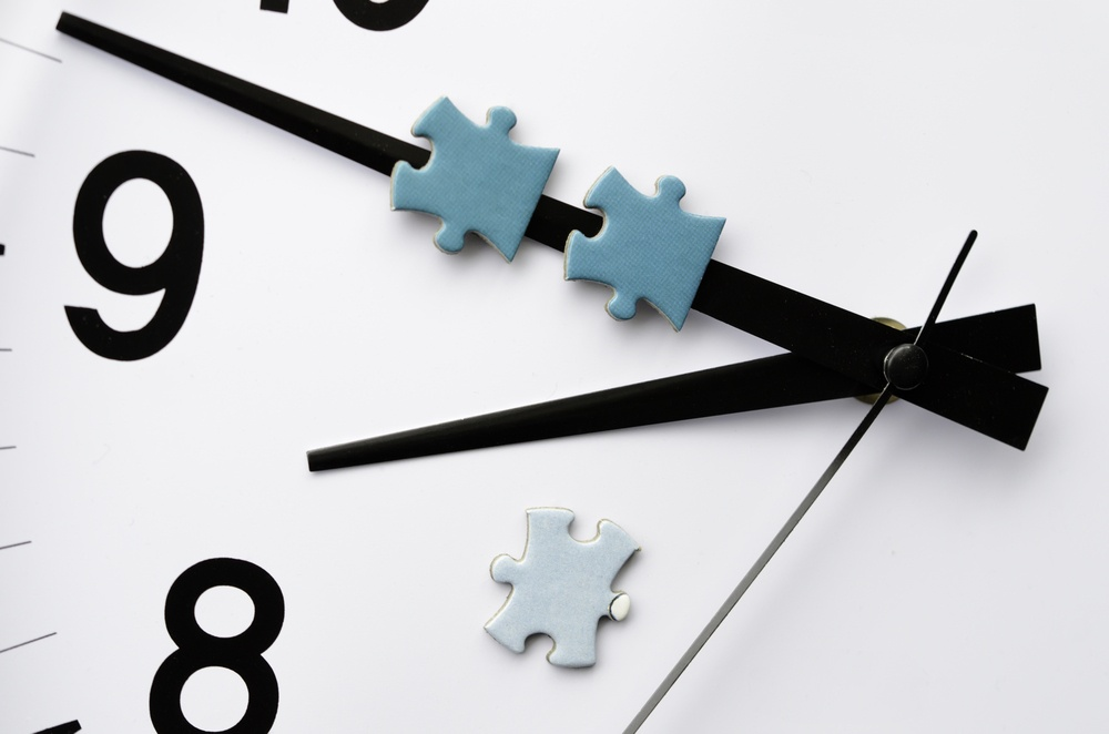 Delivery time Minute hand of analog electric clock carries two pieces of jigsaw puzzle, with a third on the white face